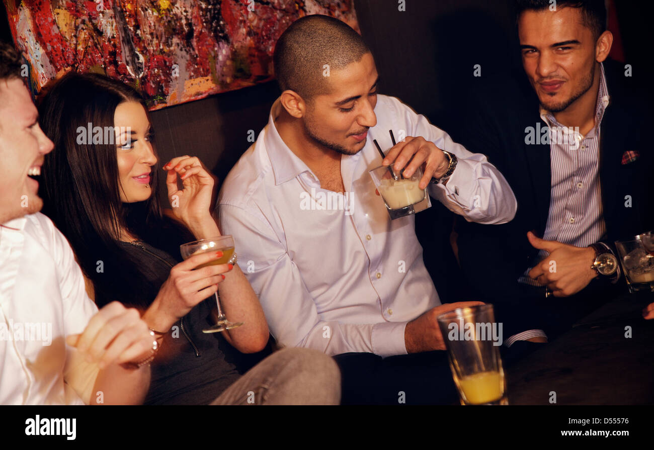 Group of men having fun together with their pretty female friend at the bar - Stock Image