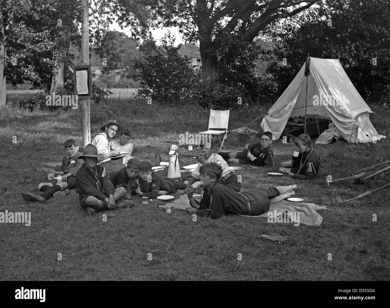 Boy scouts camp, c. 1930 with tent pitched and the scouts and scout master eating sandwiches - Stock Image