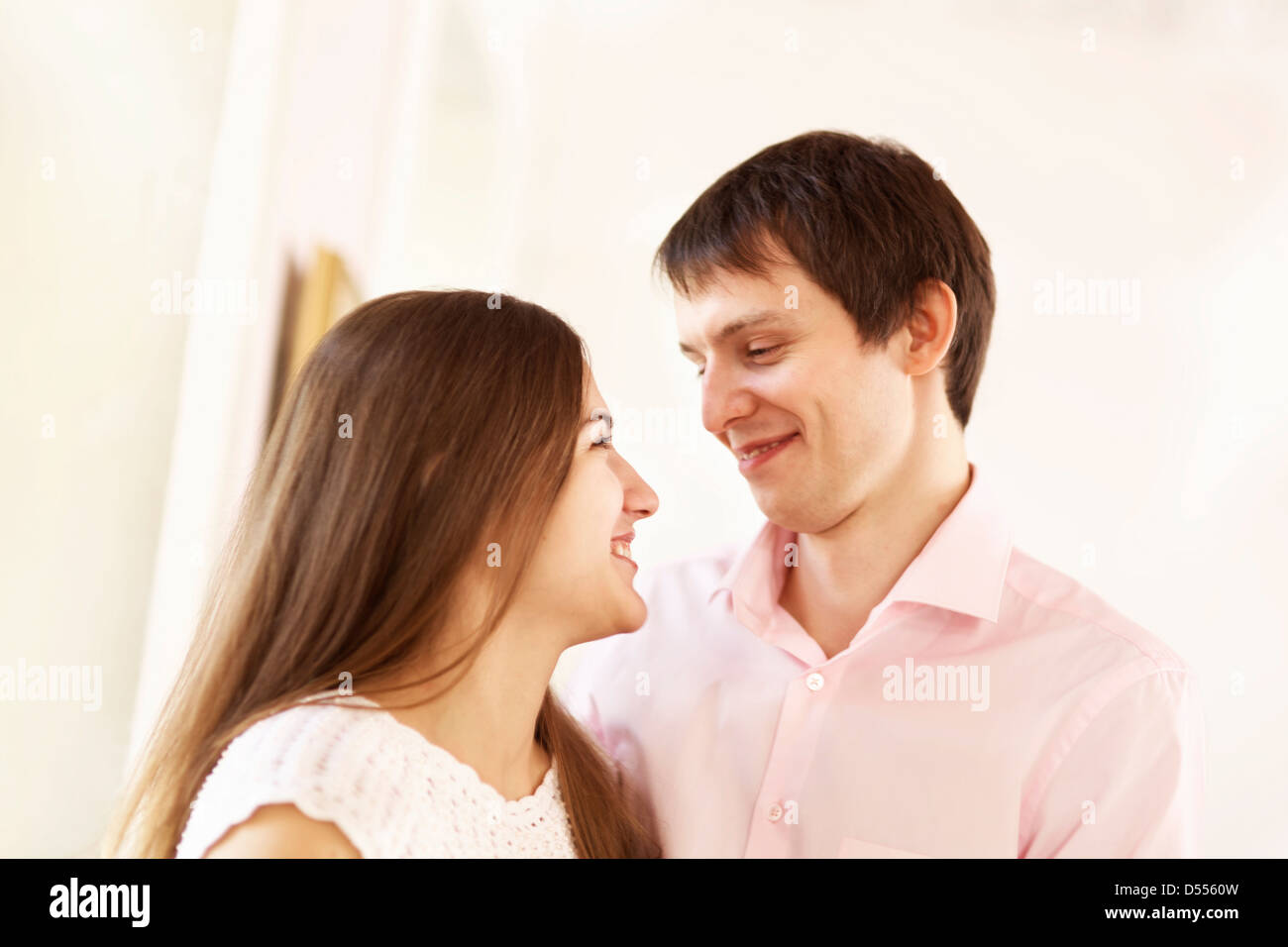 Couple smiling together indoors - Stock Image