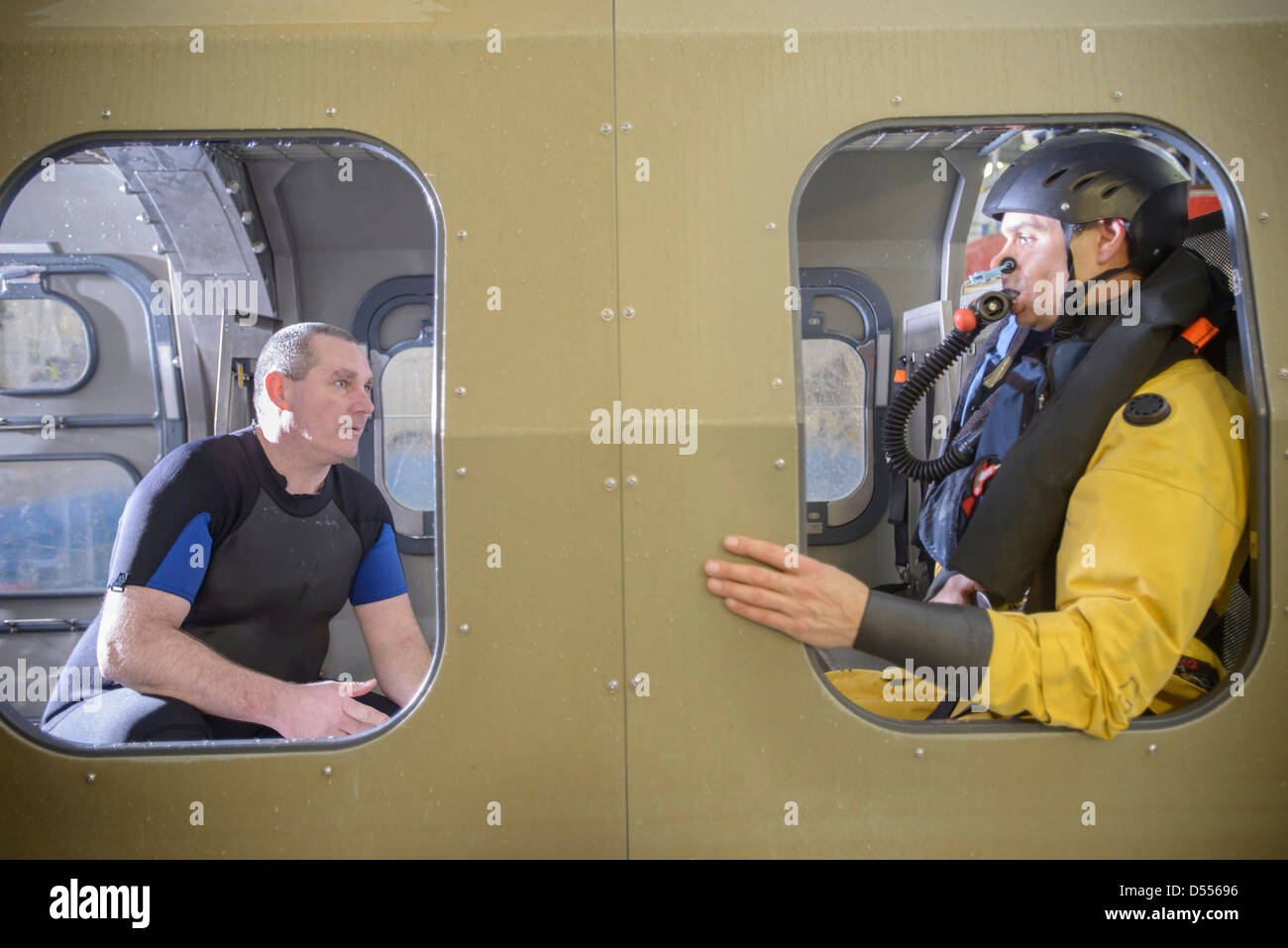 Oil workers in simulated helicopter - Stock Image