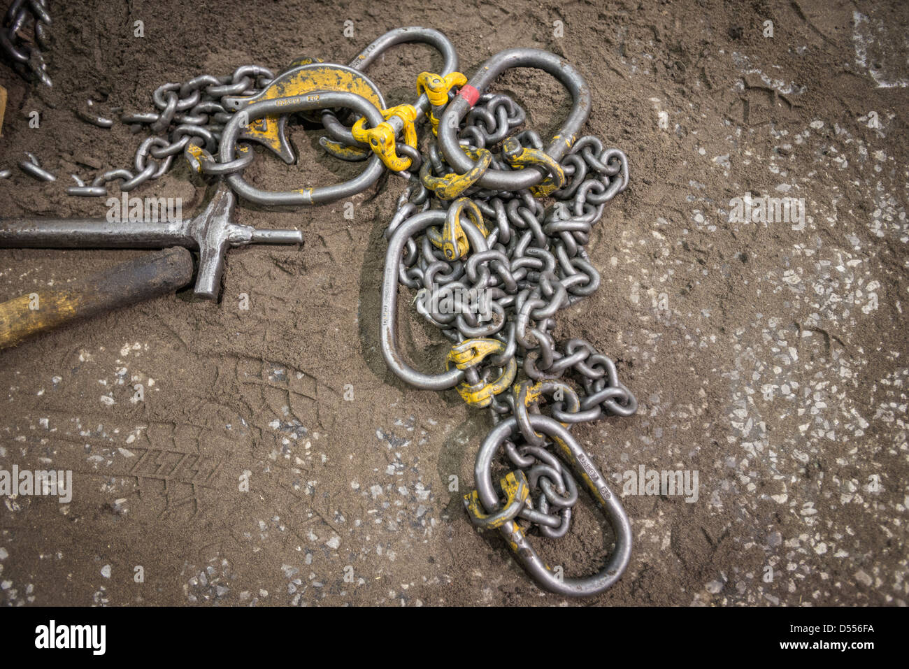 Metal chain on dirt floor - Stock Image