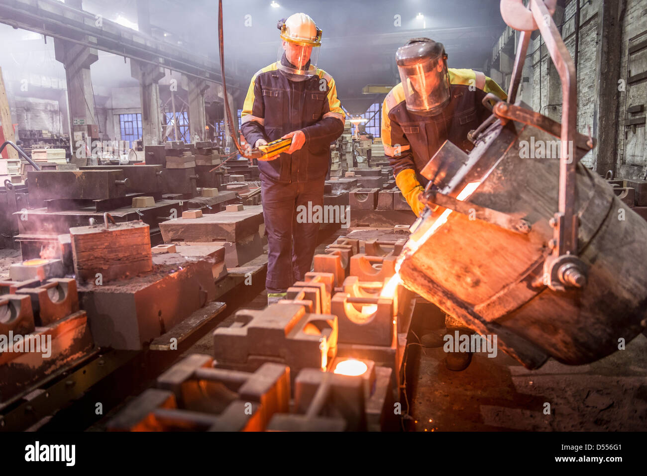 Workers pouring molten metal in foundry - Stock Image