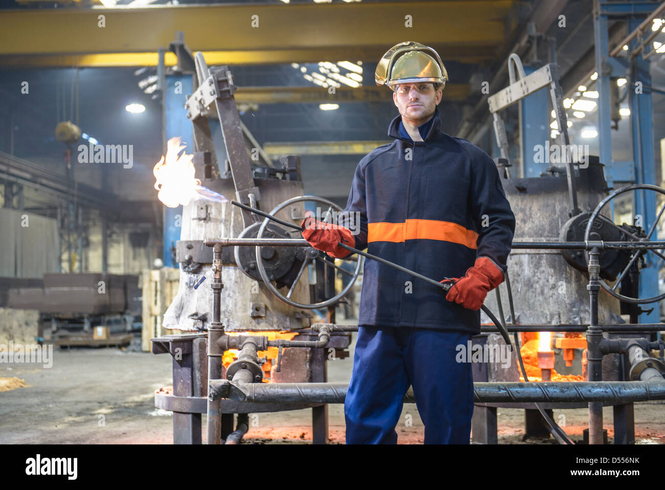 Worker holding flame gun in foundry - Stock Image