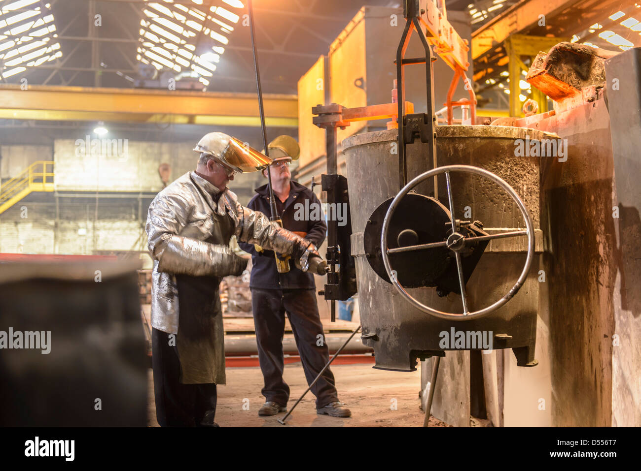 Workers with vat of molten metal - Stock Image