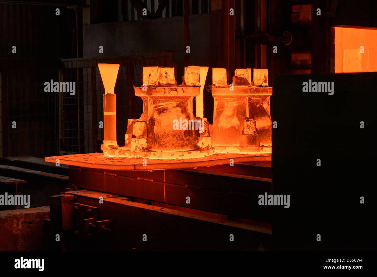 Metal casings glowing in foundry - Stock Image