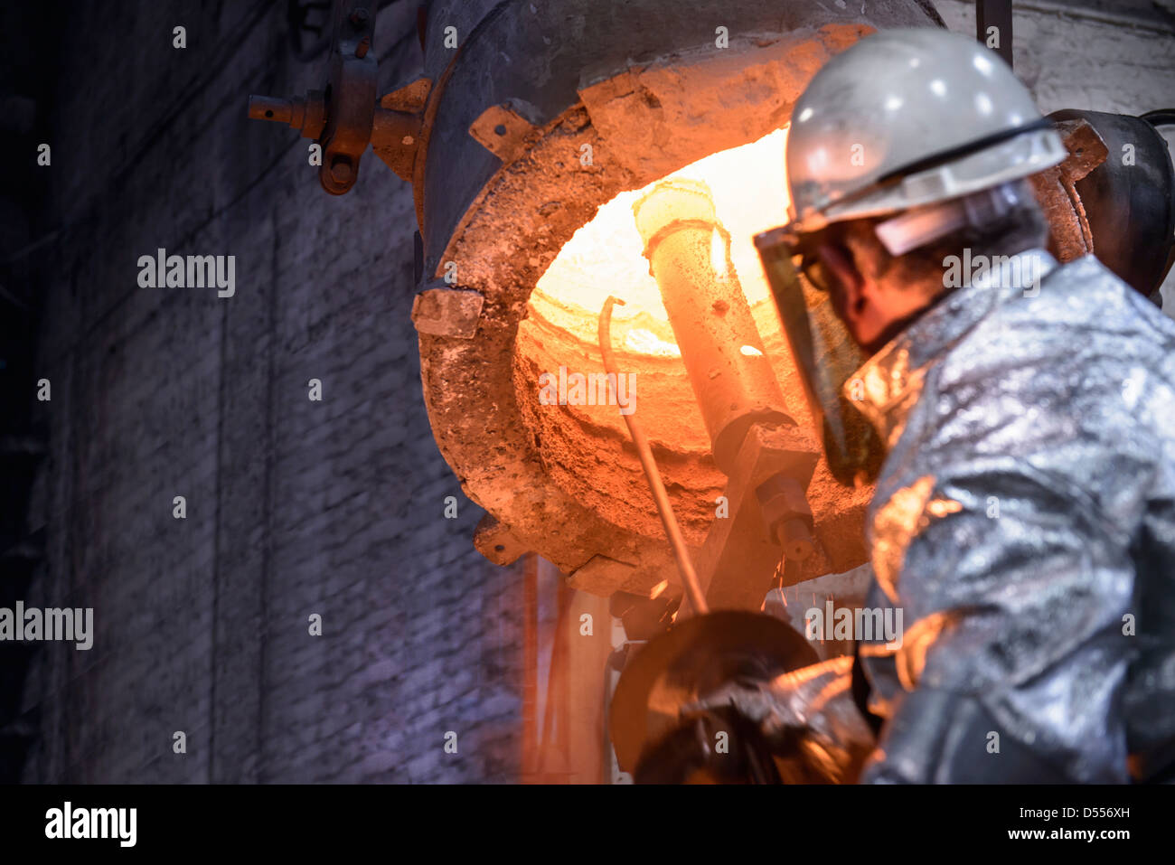 Worker cleaning metal flask in foundry - Stock Image