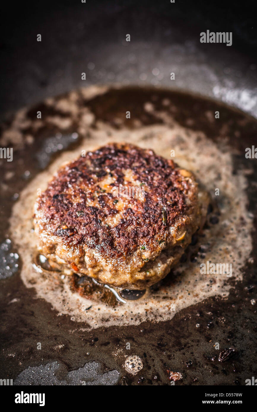 Close up of meat frying in pan Stock Photo