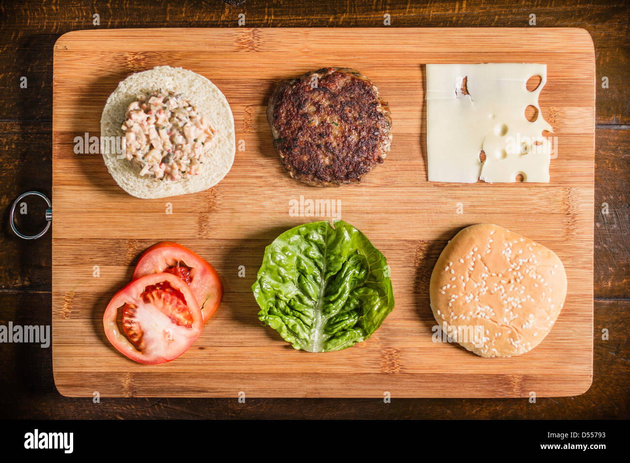 Table with hamburger and condiments - Stock Image