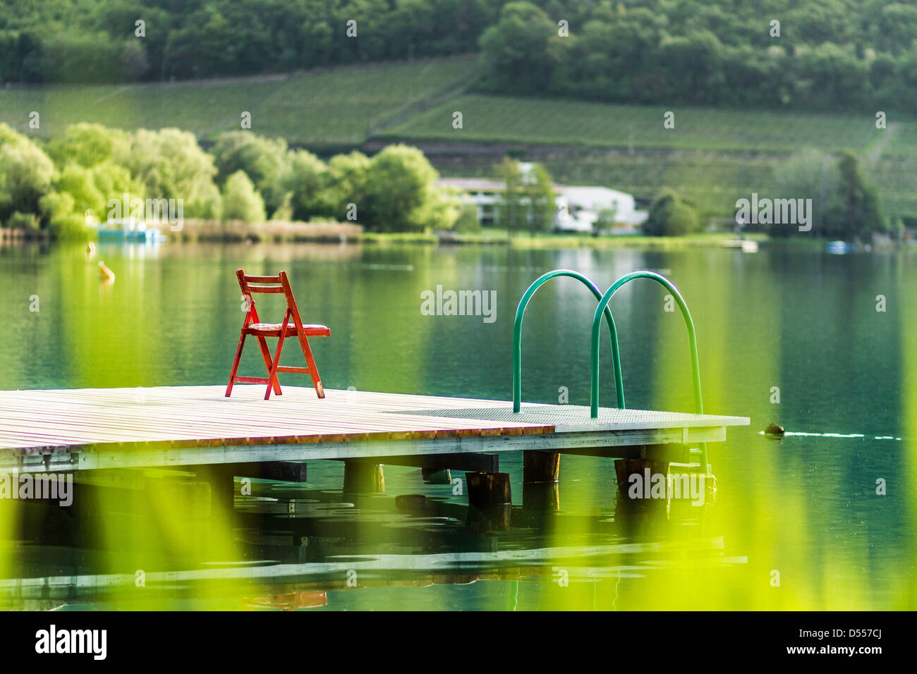 Chair on wooden pier in still rural lake - Stock Image