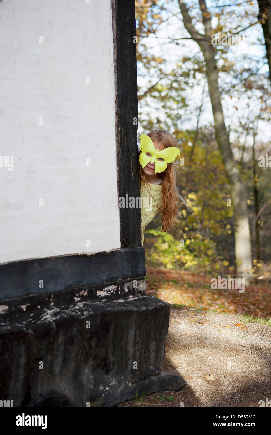 Girl wearing butterfly mask outdoors - Stock Image