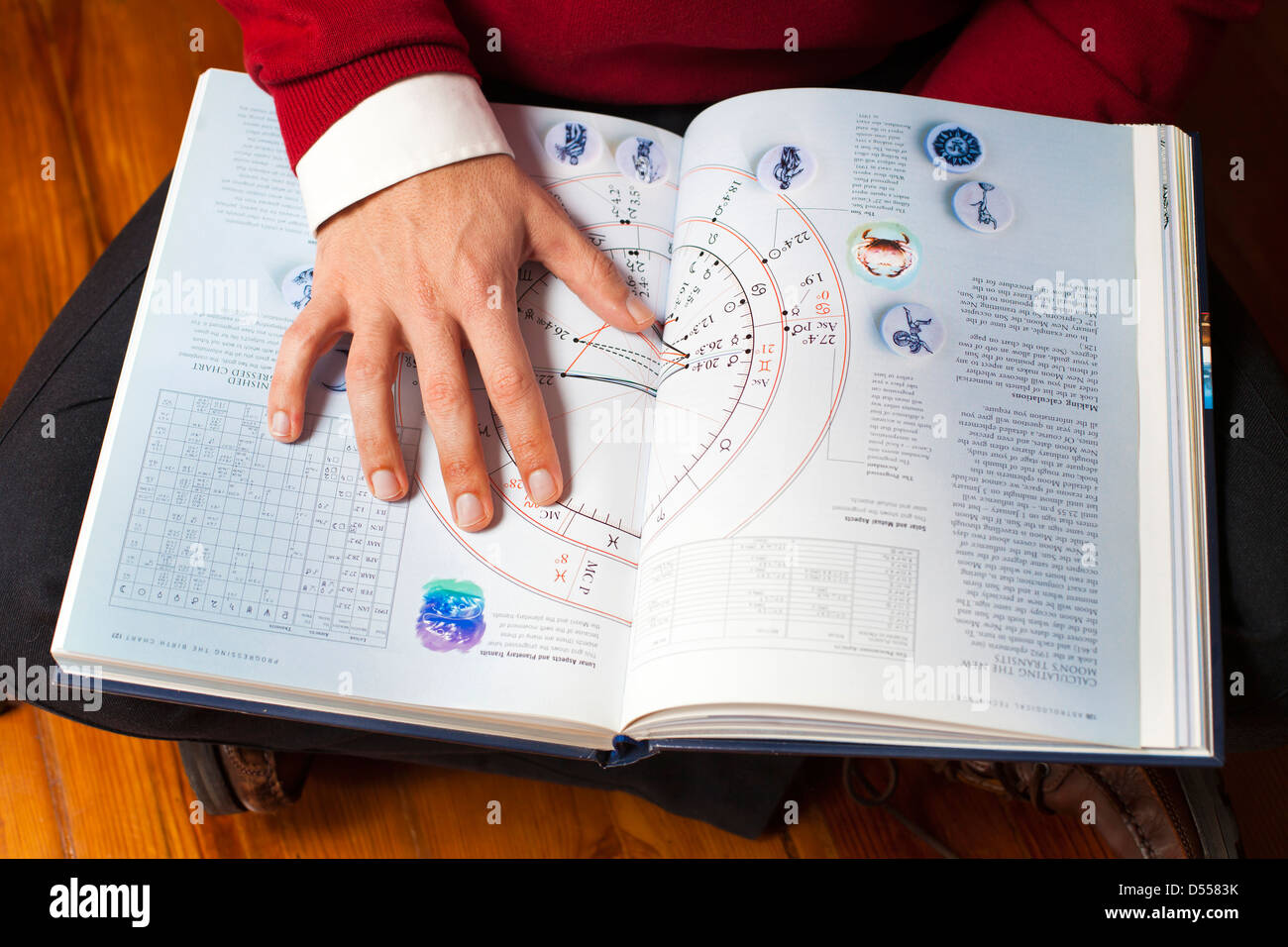 Man with astrology book. - Stock Image