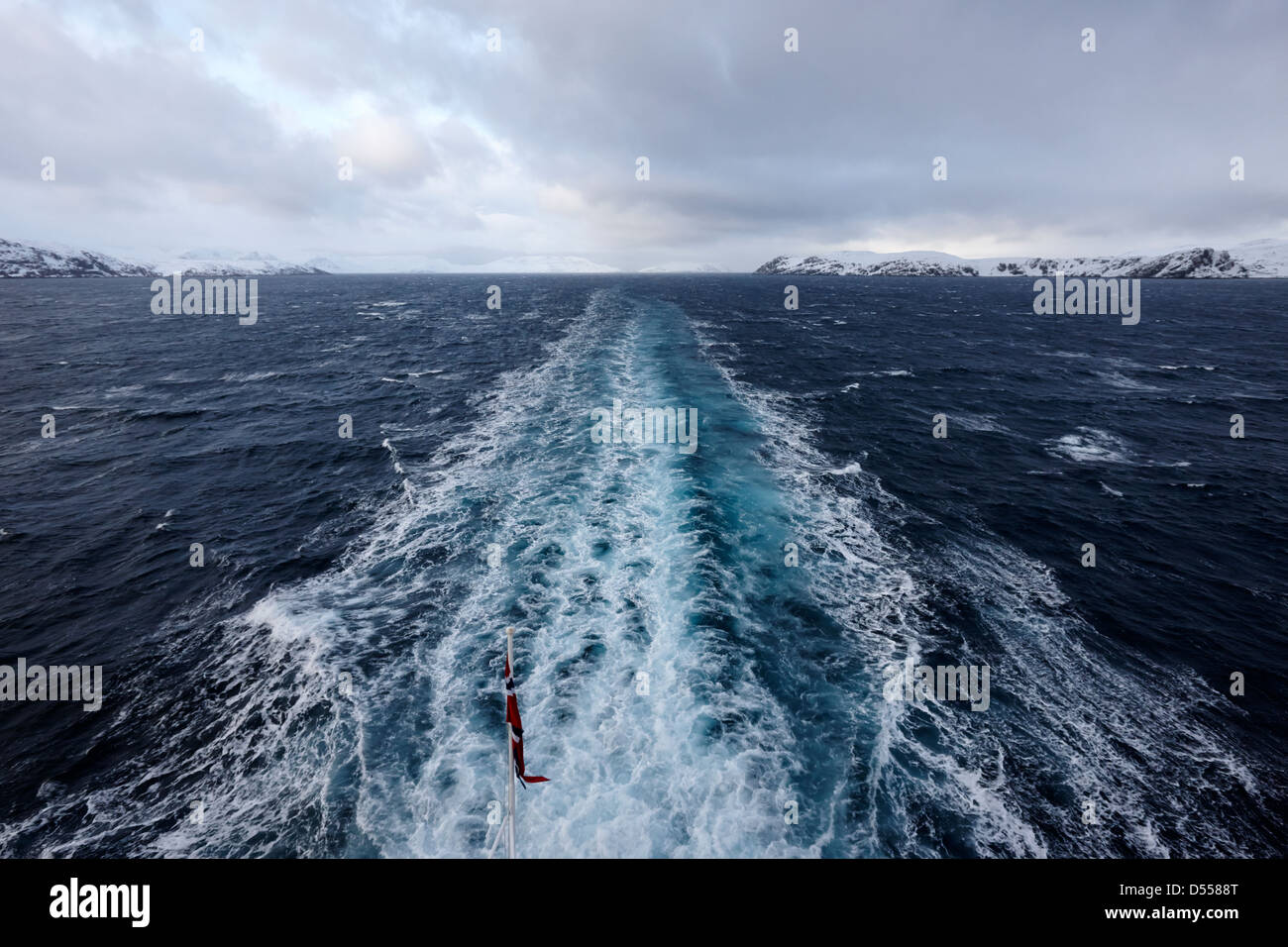 ships wake in the sea with snow covered cliffs and rugged arctic coastline northern norway europe - Stock Image