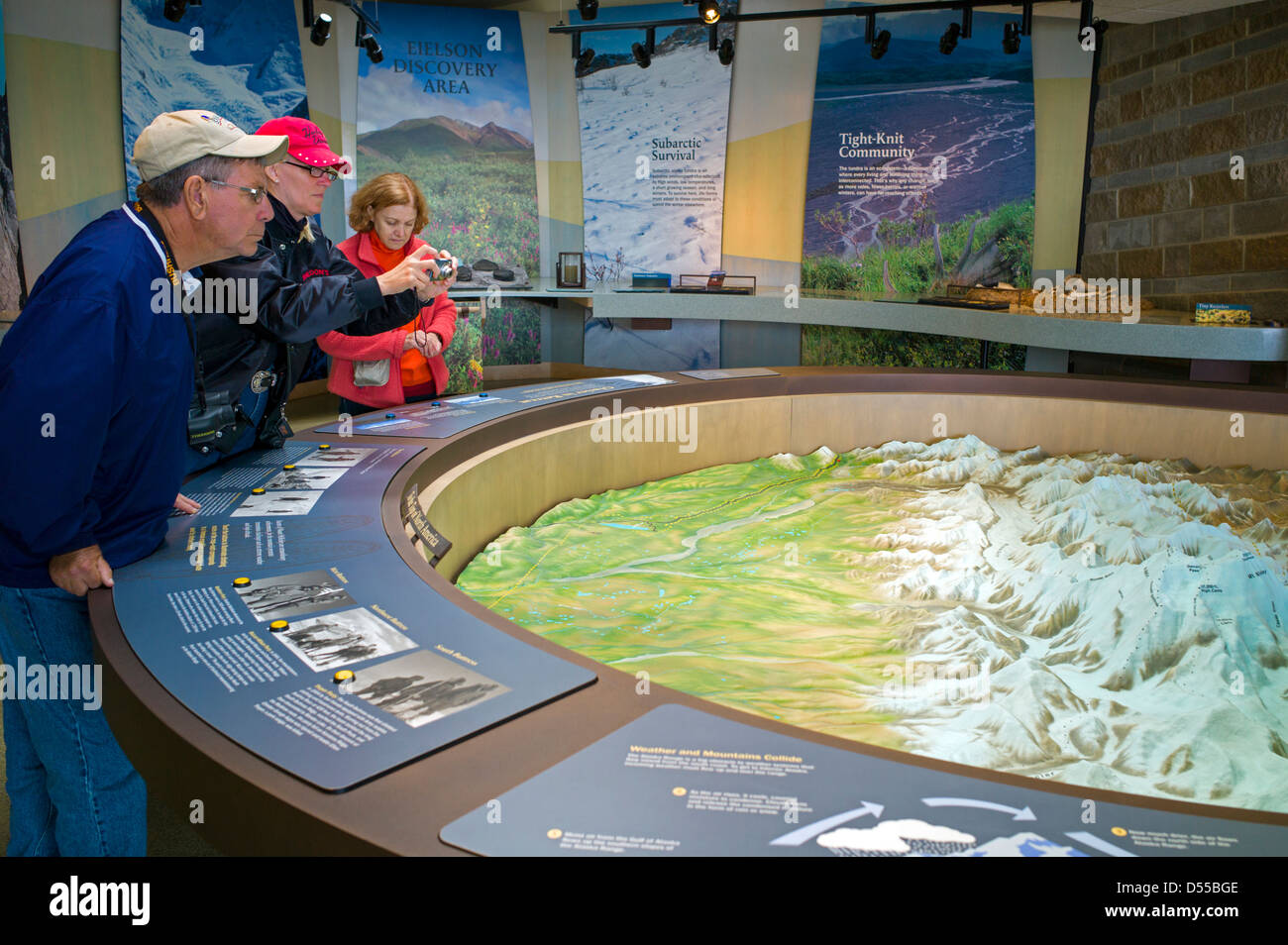 Park visitors view a three dimensional topographical map on display, Eielson Visitor Center, Denali National Park, - Stock Image