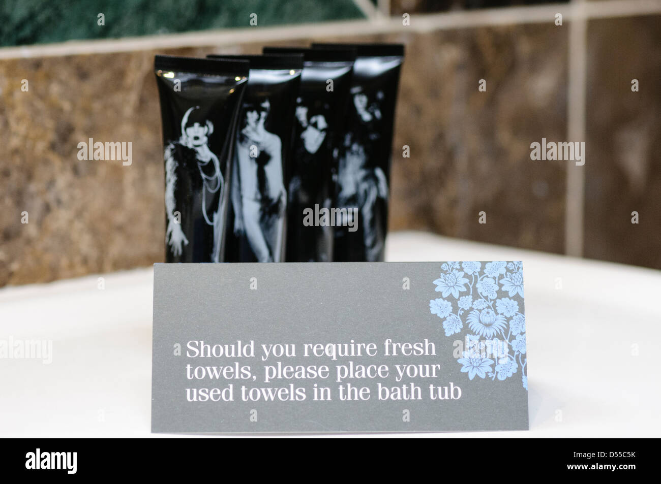 A sign in a hotel bathroom advising guests to place used towels in the bath tub should fresh ones be required. - Stock Image