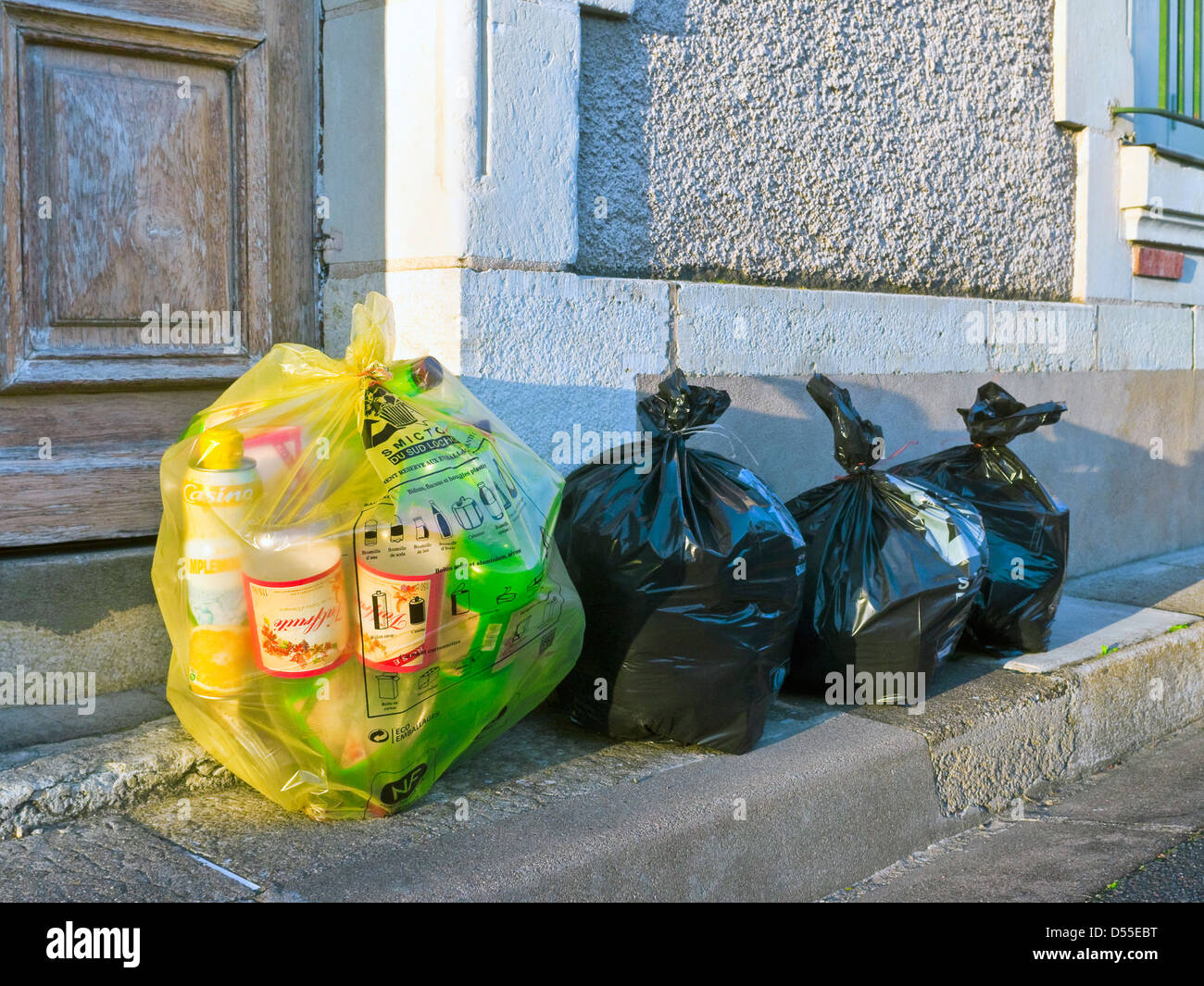 Yellow and black domestic rubbish sacks awaiting collection - France. - Stock Image