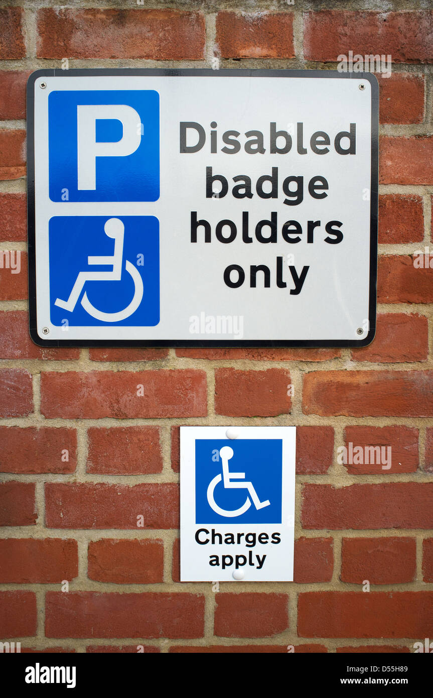 Parking for disabled badge holders only with charges apply signs - Stock Image