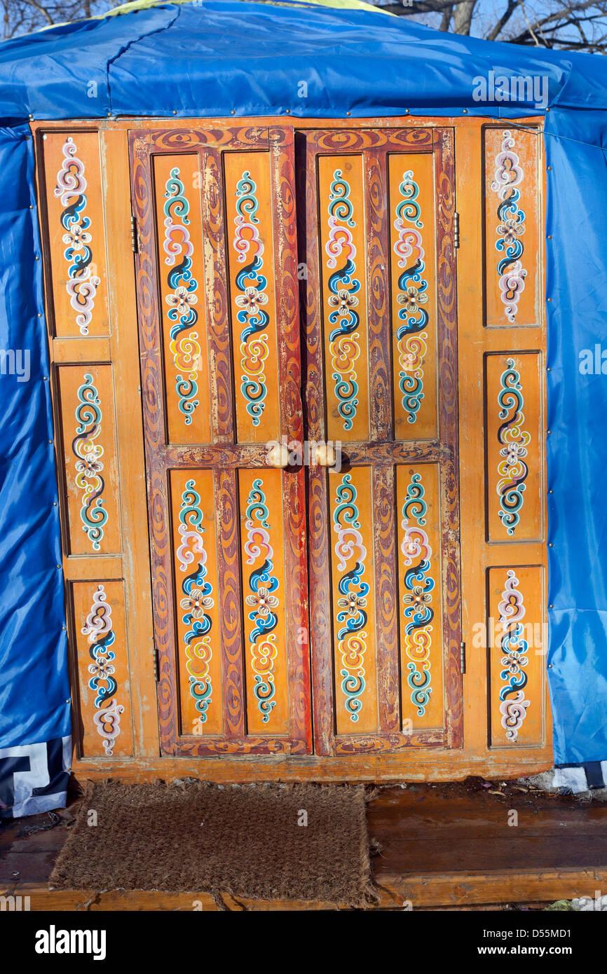 Wooden decorated orange door in kazakh yurt - Stock Image