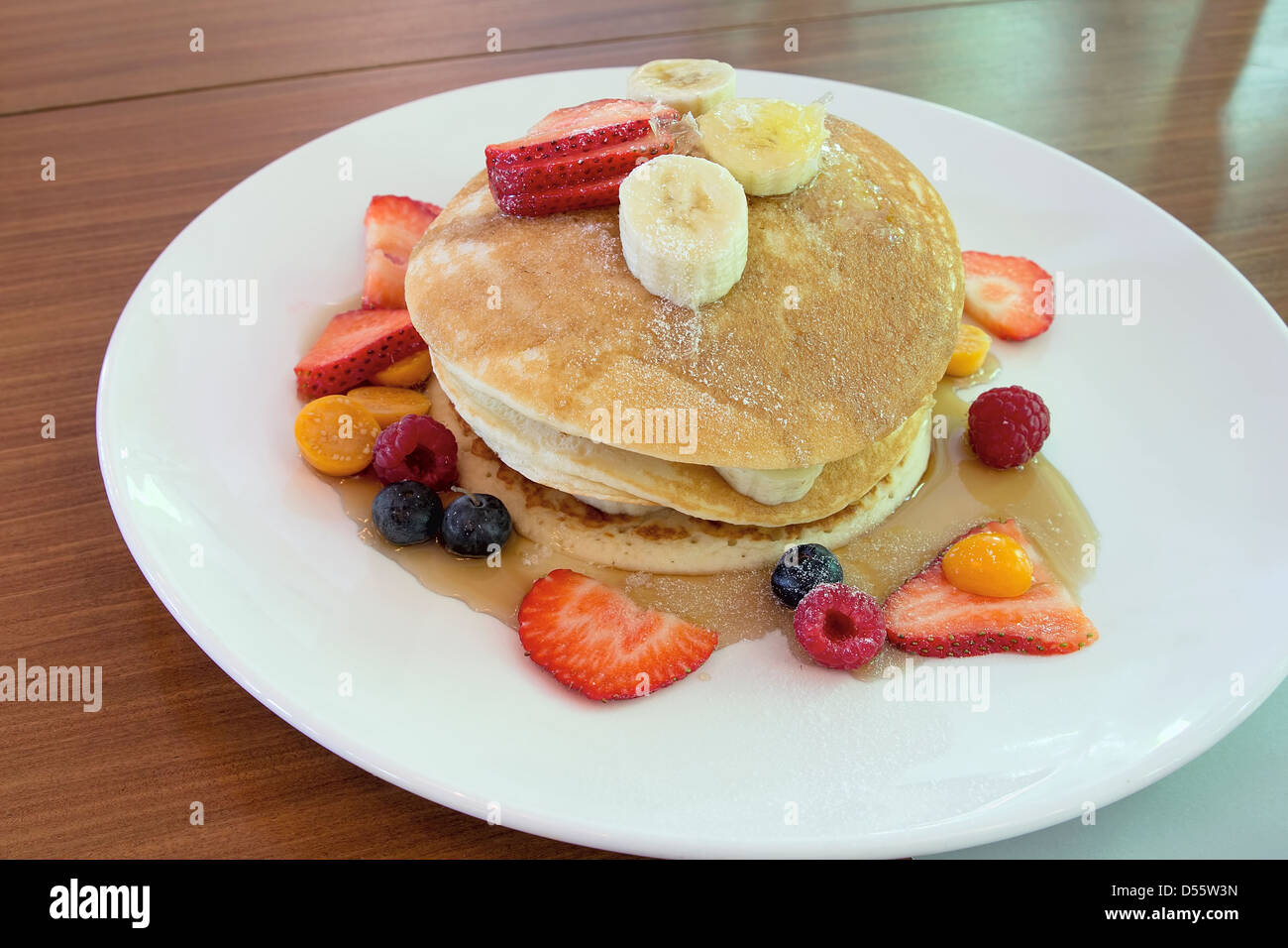 Hotcakes with Blueberries Strawberries Raspberries Banana and Honeycomb Stock Photo