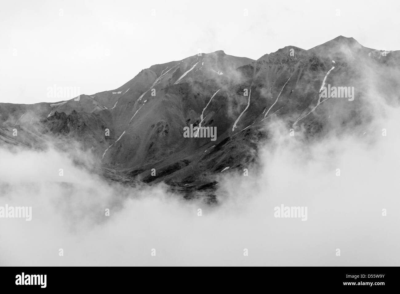 Black and white view of low clouds, mist and fog partially obscure the Alaska Range, Denali National Park, Alaska, - Stock Image