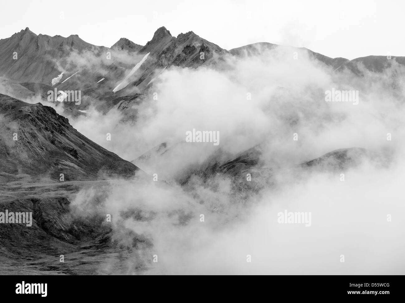 Black and white view of low clouds, mist and fog partially obscure the Alaska Range, Denali National Park, Alaska, Stock Photo
