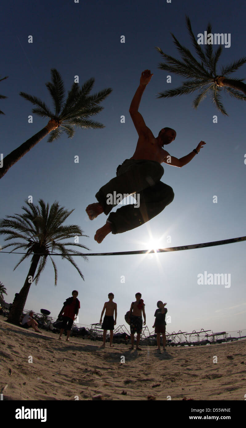 A young man practice slackline on the beach. Slacklining is a practice in balance that typically uses nylon or polyester Stock Photo