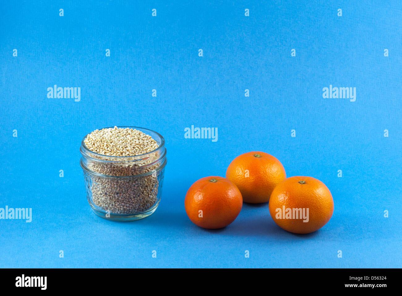 Jar of organic Quinoa (Chenopodium quinoa) with organic mandarin oranges - Stock Image