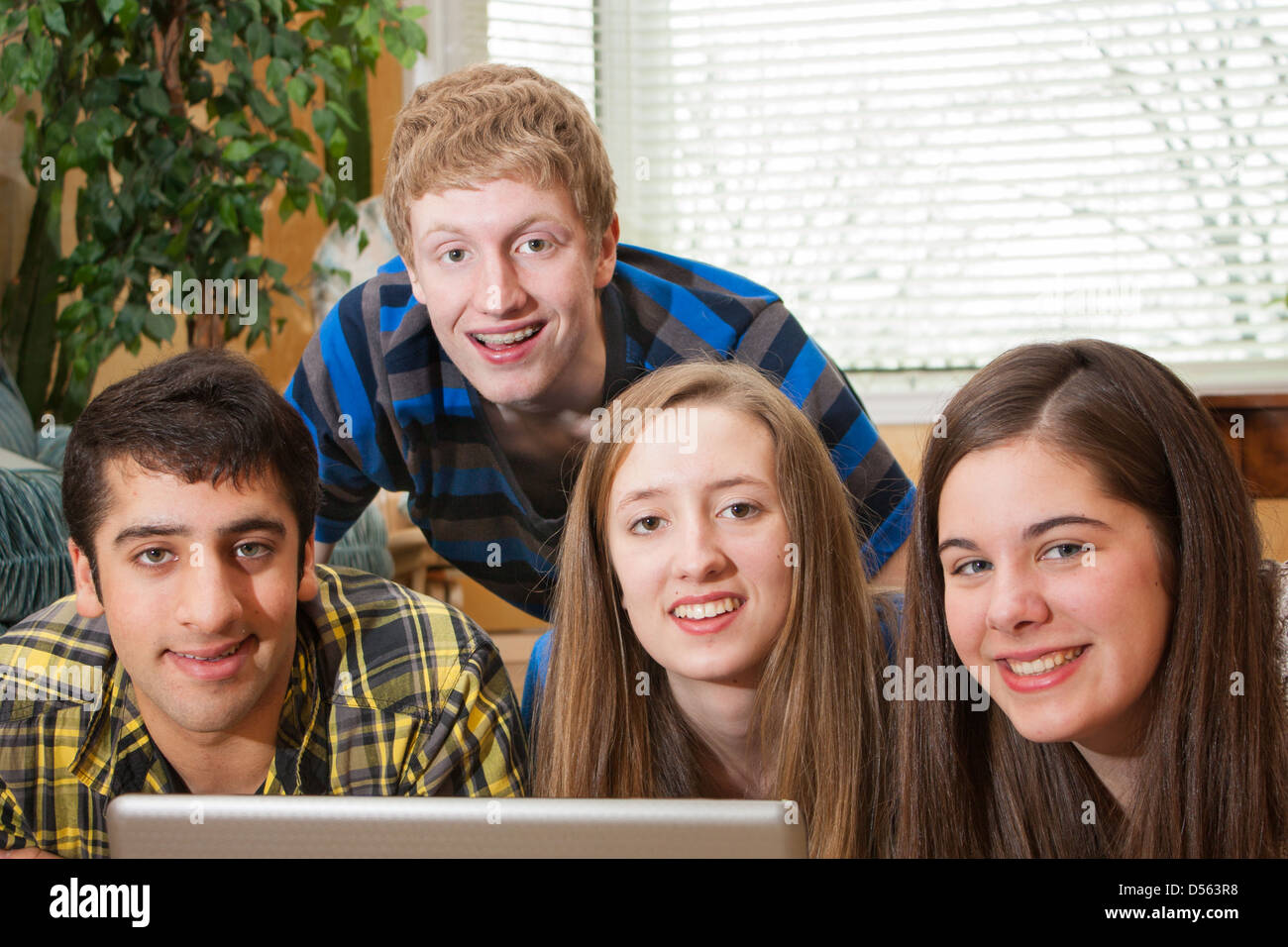 A diverse group of teenagers gathered around a laptop in a home setting looking at the camera - Stock Image