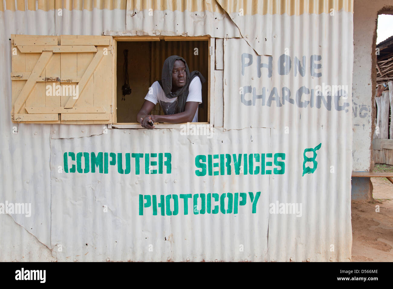 Man awaiting business in a mobile phone charging booth, Yala, Kenya. - Stock Image