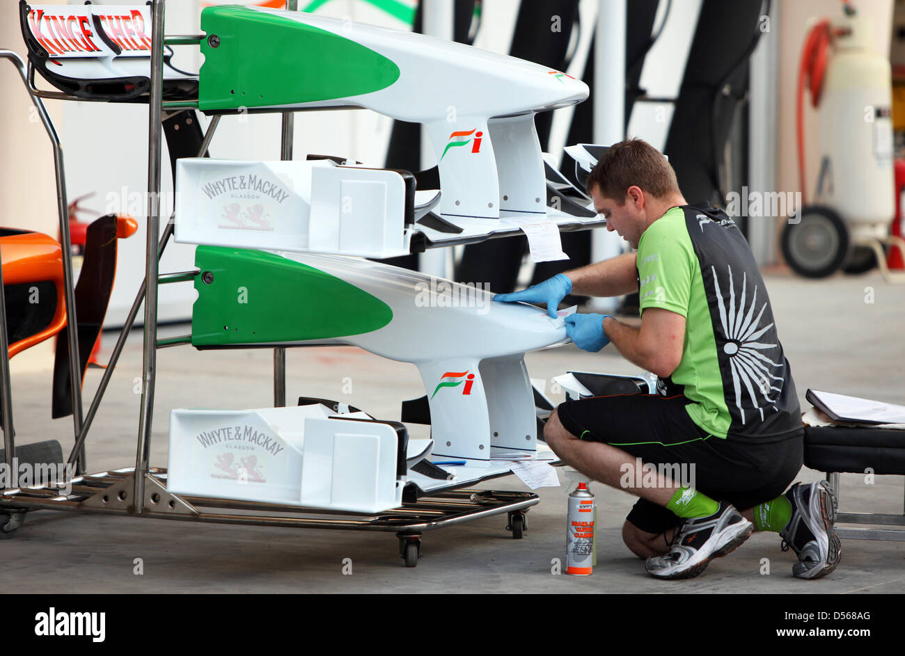 A Mechanic Of Force India Attaches Stickers To Front Wings