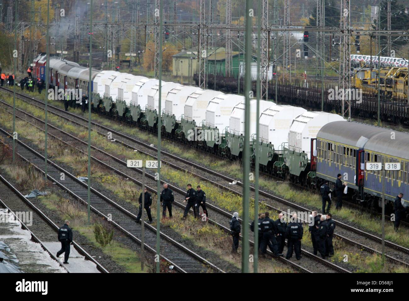 Police officers dressed in riot gear have break while standing next to the train that carries the Castor nuclear - Stock Image