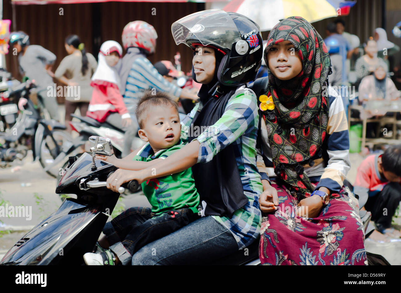 Indonesian street scene of two women and infant boy on a motorbike - Stock Image