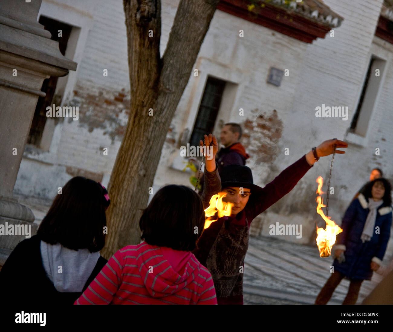 Female fire eating juggler entertainer performing at dusk in Mirador San Nicolas Granada Andalusia Spain Europe - Stock Image