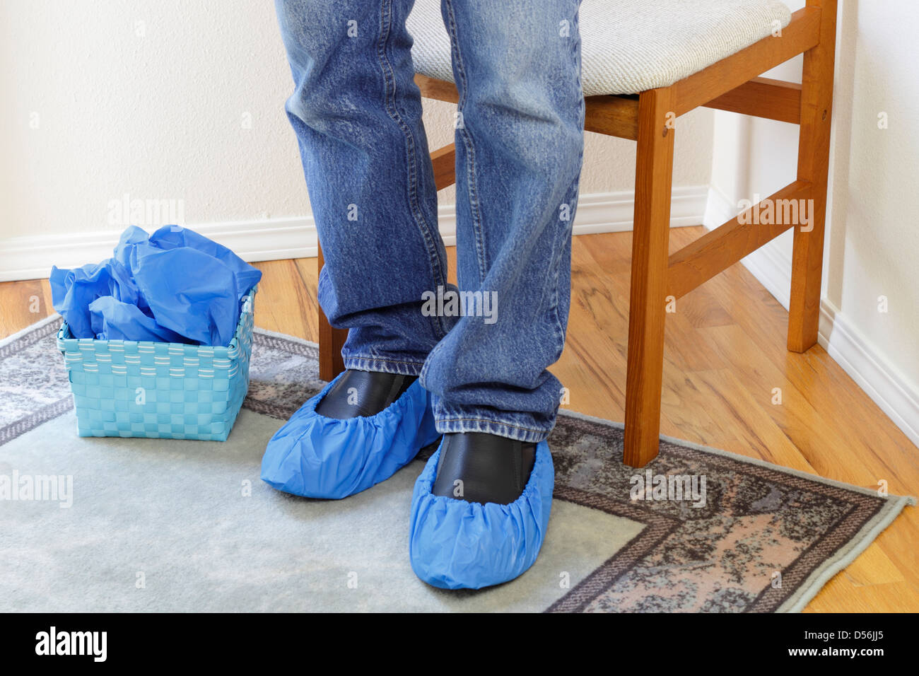 Male legs wearing jeans seen from the knees down to the floor wearing blue floor protectors called booties on both - Stock Image