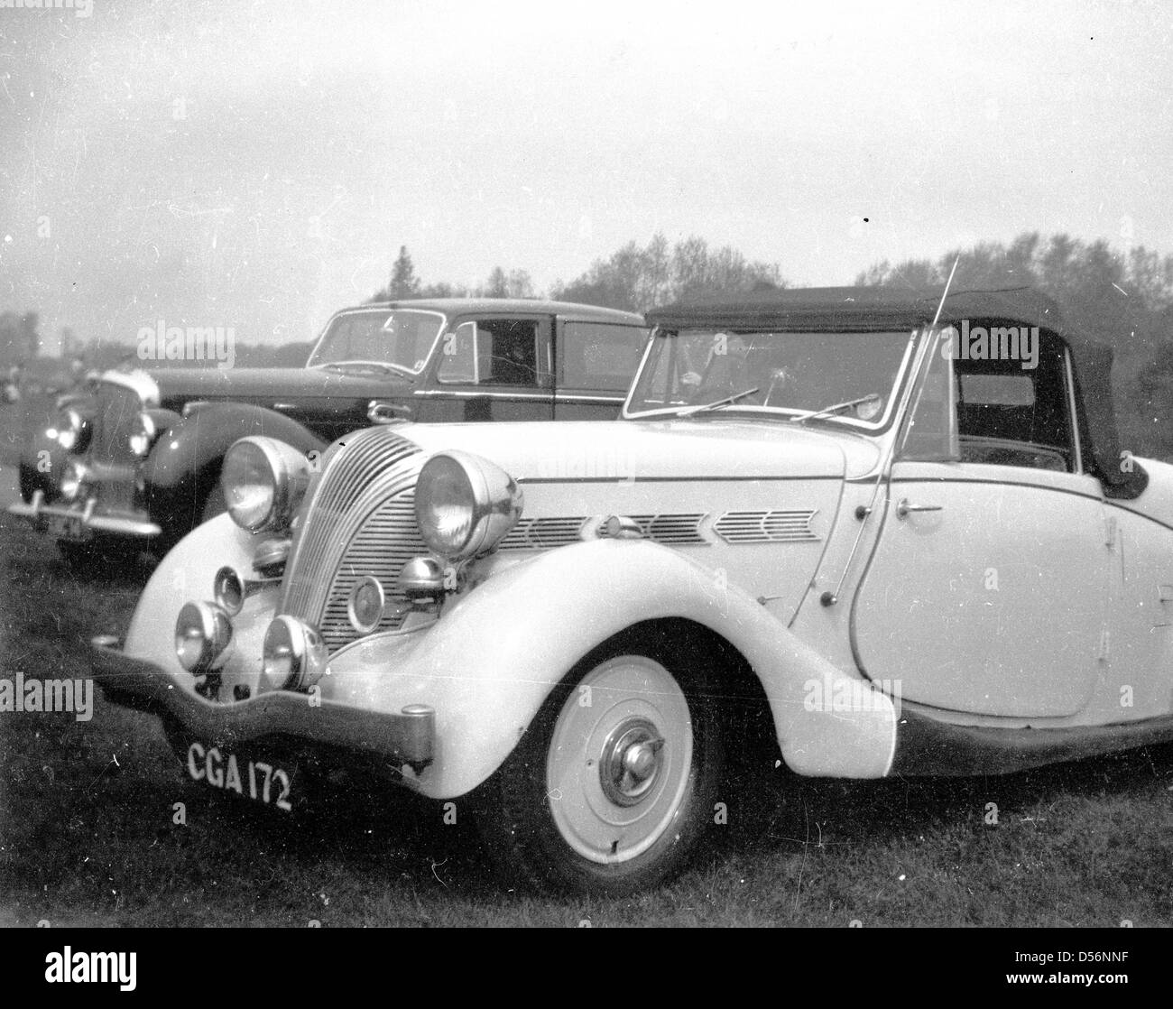 Historical 1950s. England. Two cars from this era parked beside each other in a field. - Stock Image