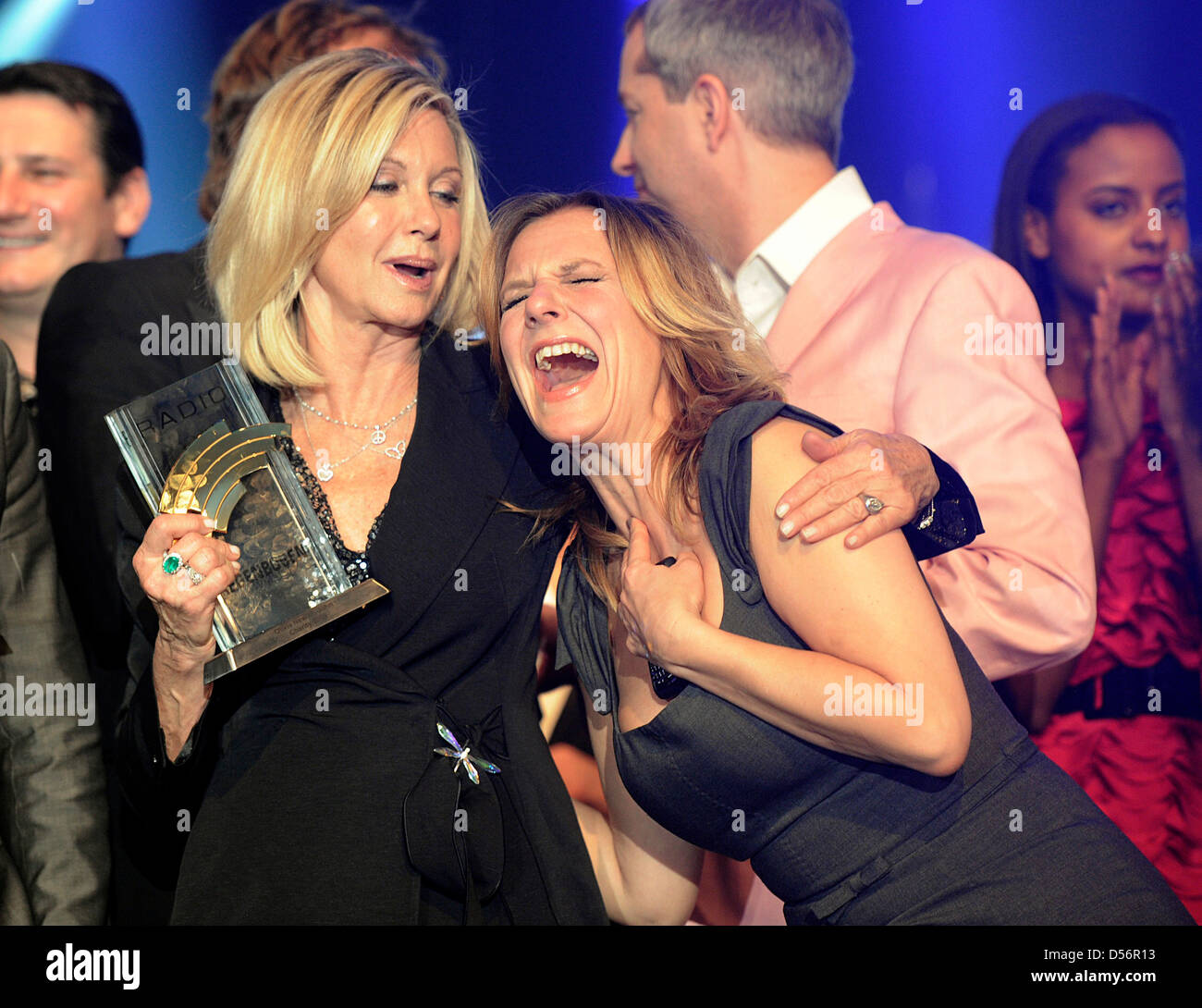 English-born singer and actress Olivia Netwon-John (L) smiles with her Radio Regenbogen Award and German TV host Stock Photo