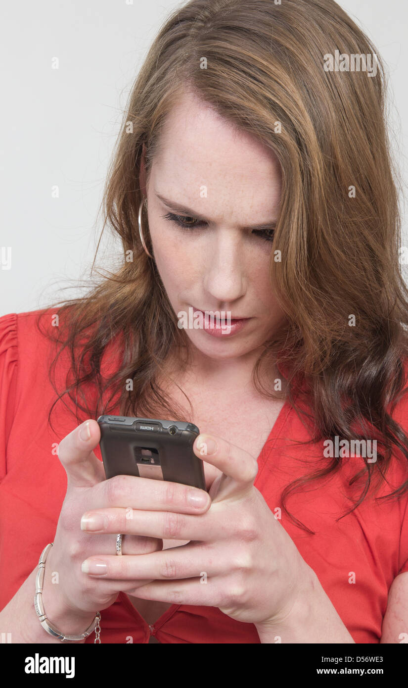 YCaucasian young woman looking at cell phone display, looking worried, IAD, cellphone addict or having a blurred - Stock Image