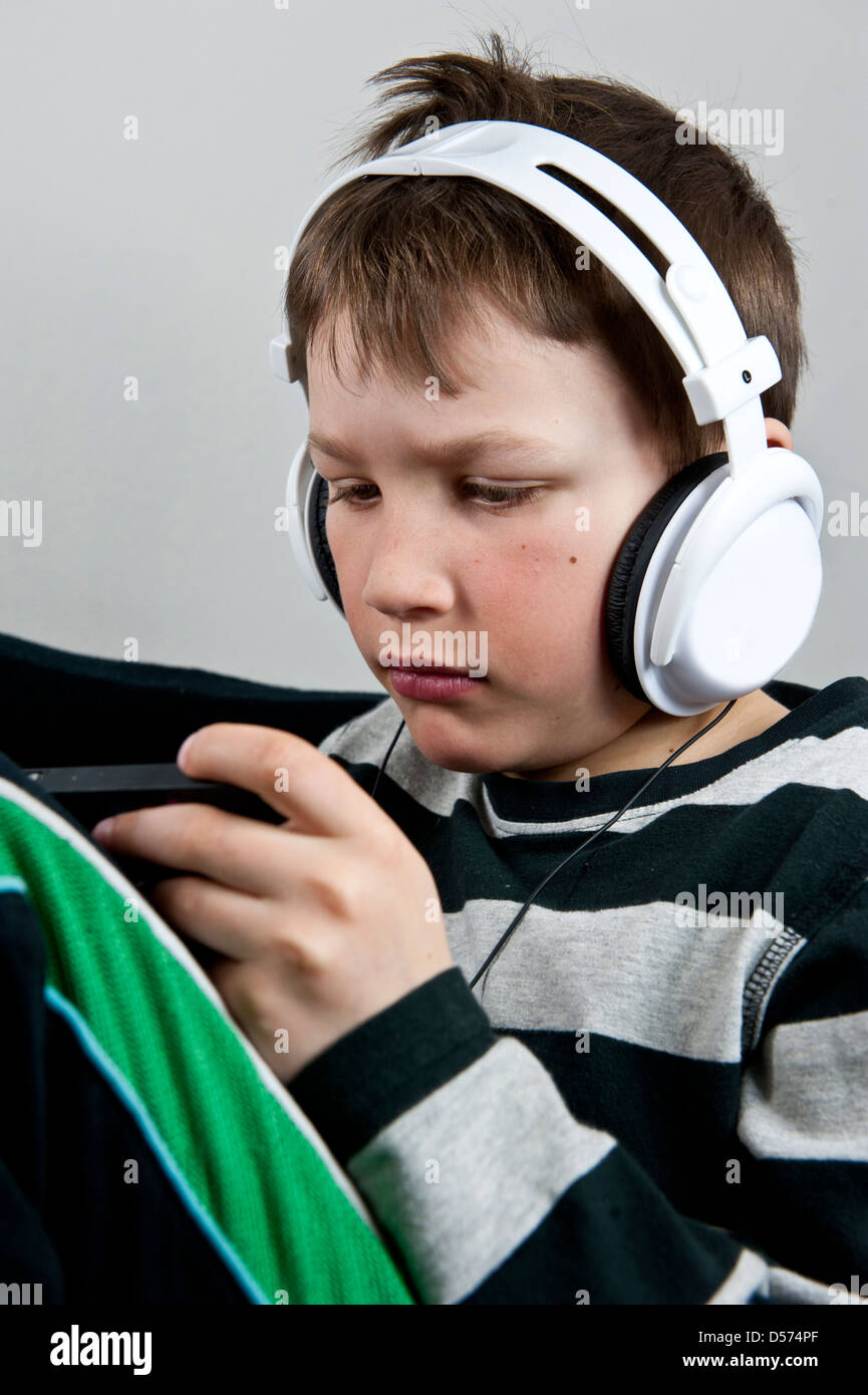 Young boy listening to music in earphones wile playing or texting on a cellphone - Stock Image