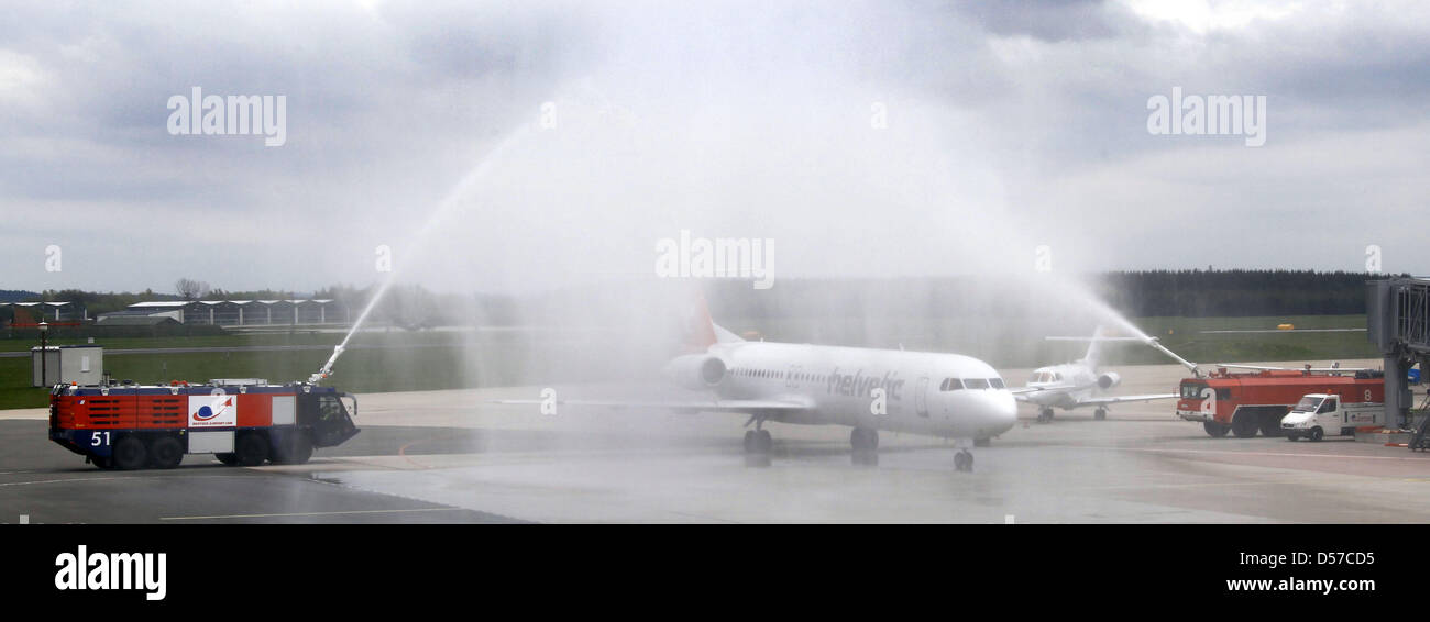 An airplane of the airline Helvetic Airways is welcomed with a water fountain at the airport Rostock-Laage in Rostock, - Stock Image