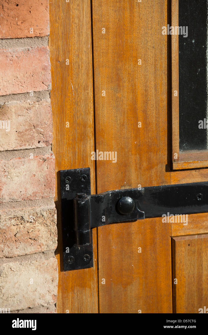 Close up of metal door hinge on an exterior door on a newly converted barn. - Stock Image