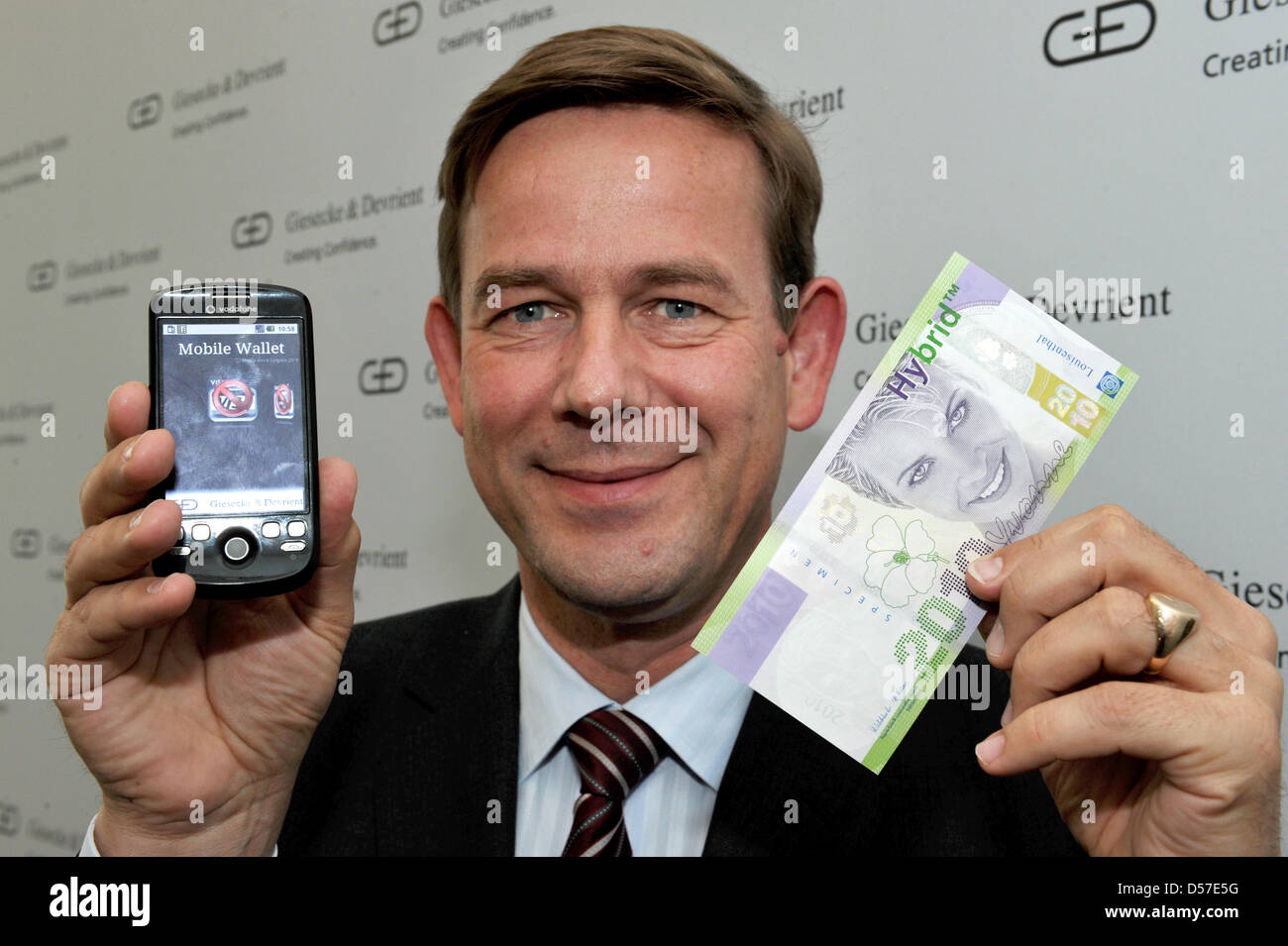 Karsten Ottenberg, CEO of bank note specialist Giesecke & Devrient, holds a mobile phone for cashless paying and Stock Photo
