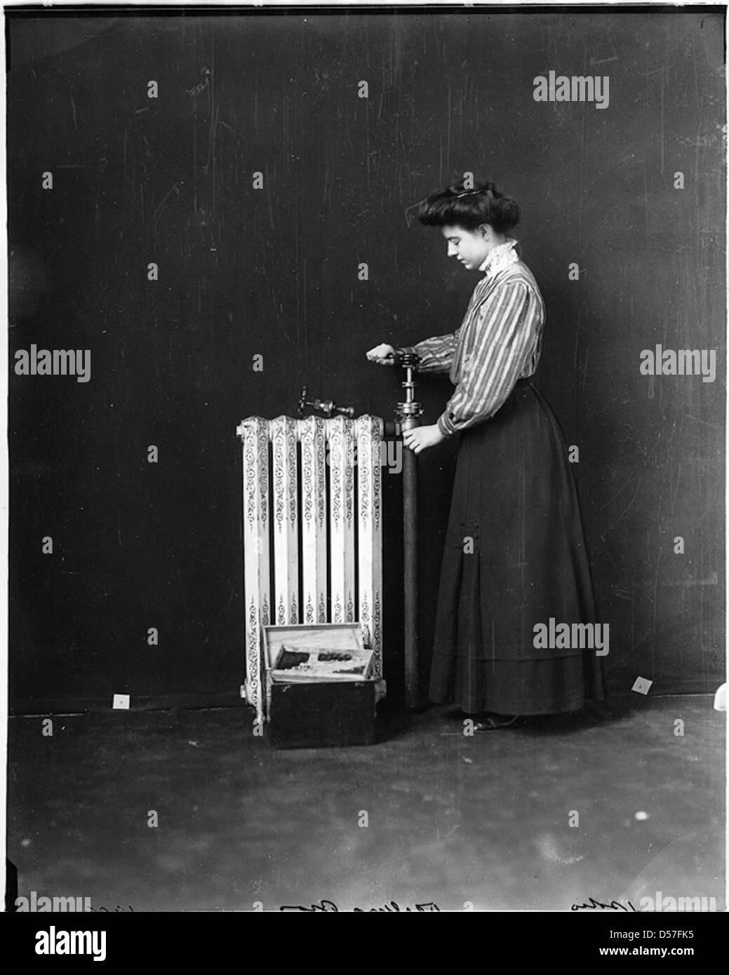 Woman repairing hot water radiator, 1909 - Stock Image