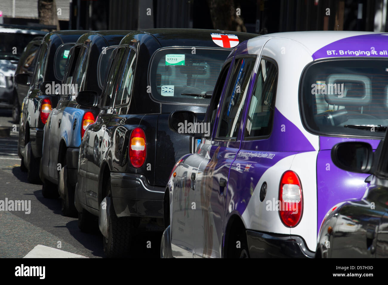 Row of black taxi cabs in the city of London, England. - Stock Image