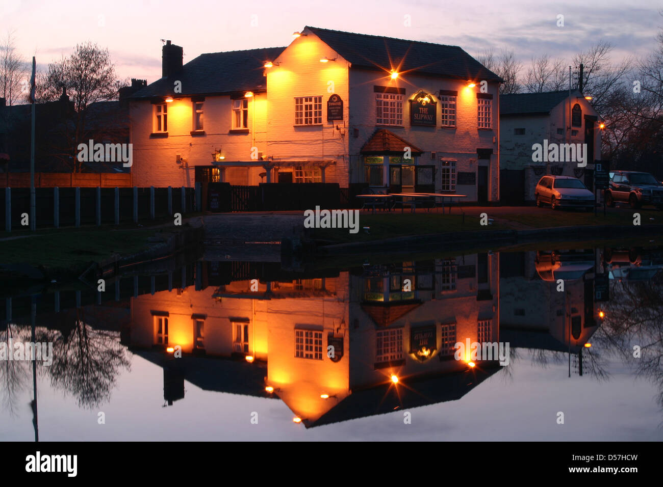 The Slipway pub reflected in the Leeds and Liverpool canal at Dusk - Stock Image