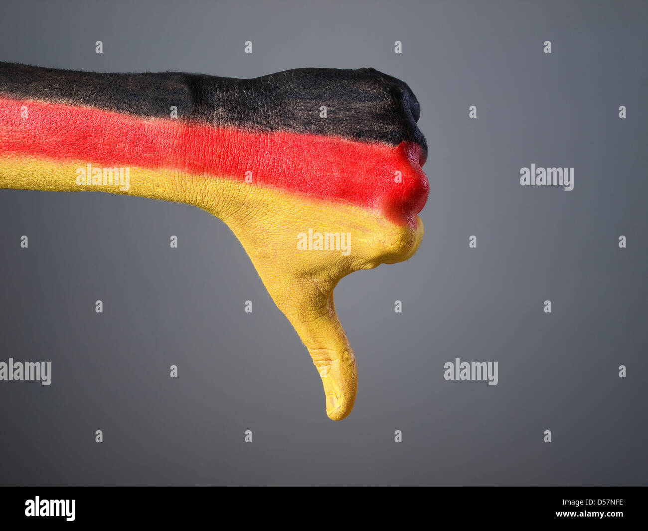 Hand painted with the flag of Germany, expressing negativity and isolated on gray background - Stock Image