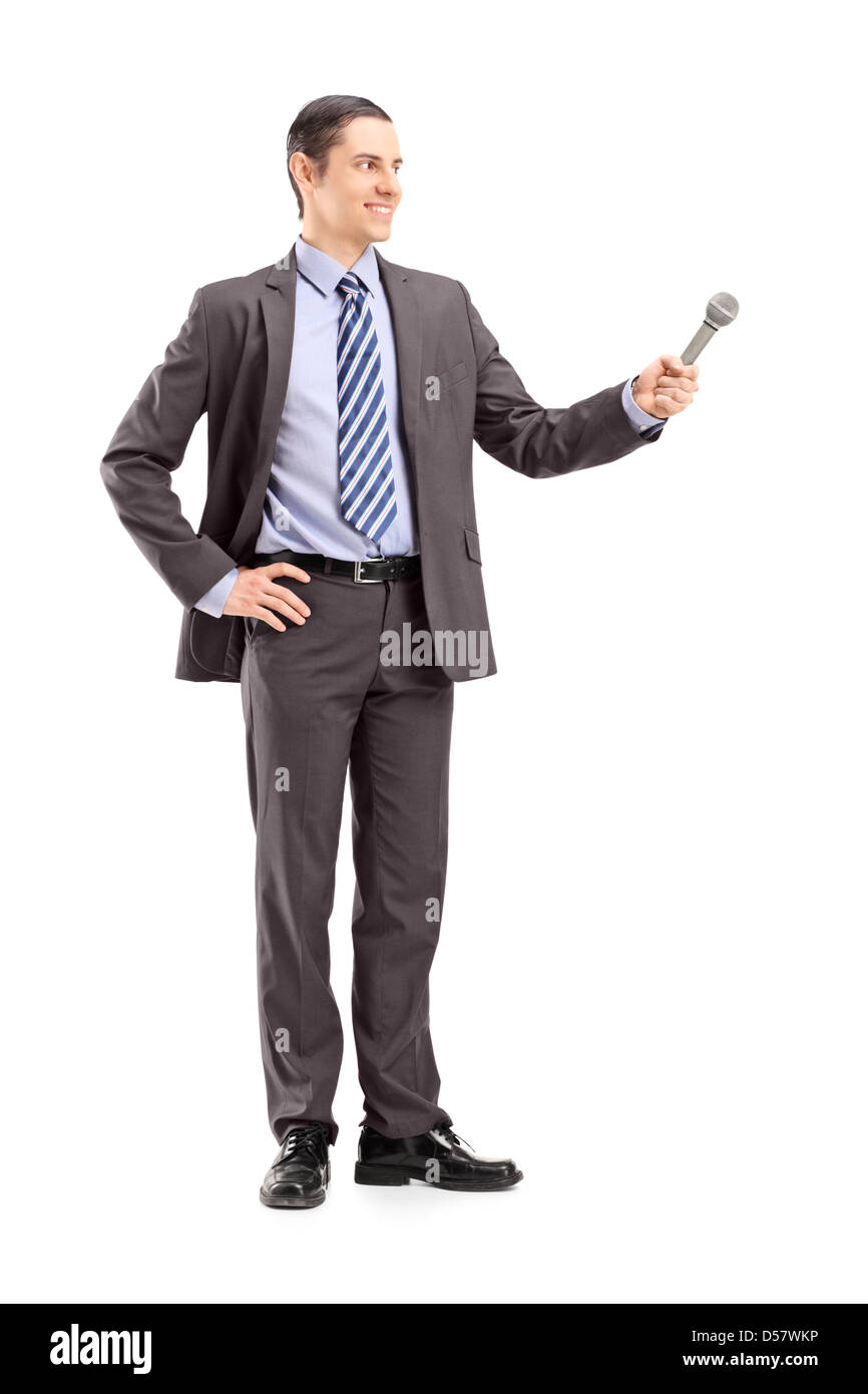 Full length portrait of a professional male reporter holding a microphone, isolated on white background - Stock Image