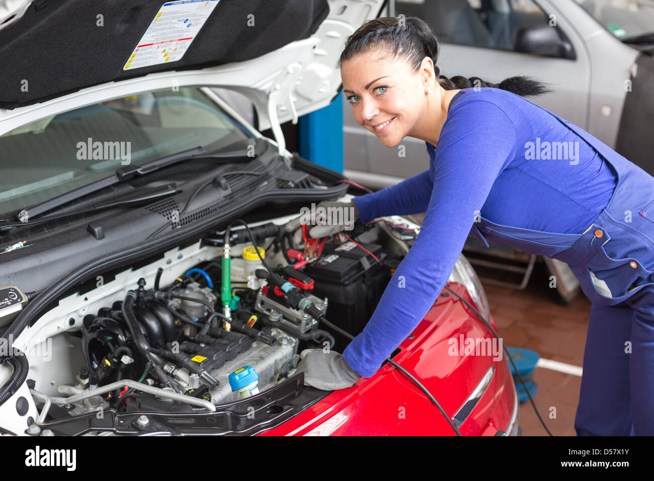 Mechanic repairing the motor or electric parts of a car in a garage - Stock Image