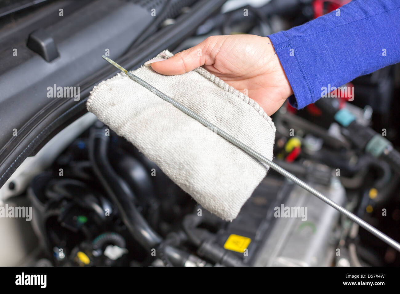 Car mechanic checking the oil of a car - Stock Image