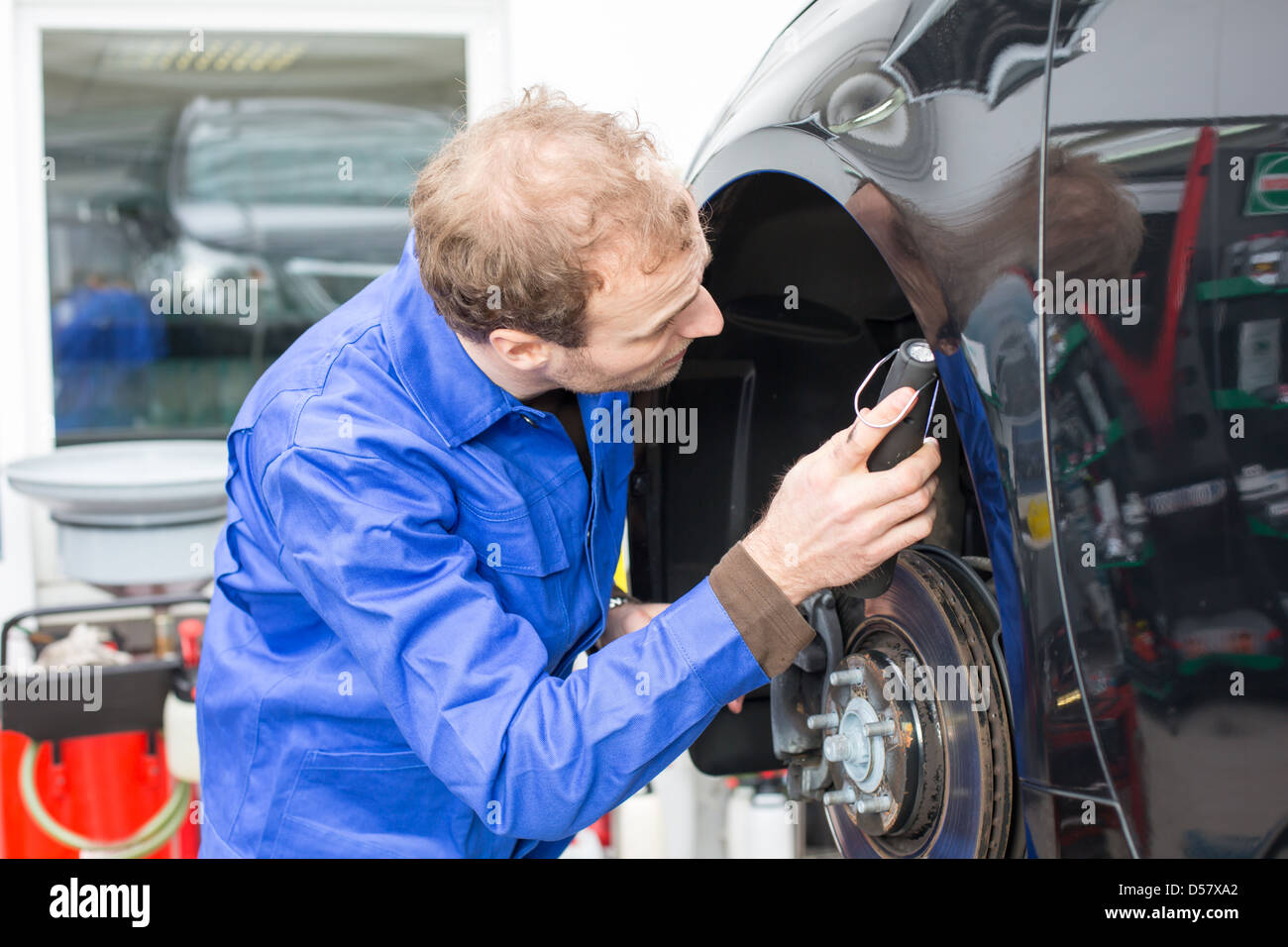 Car mechanic repairs the brakes of an automobile on a hydraulic lift Stock Photo