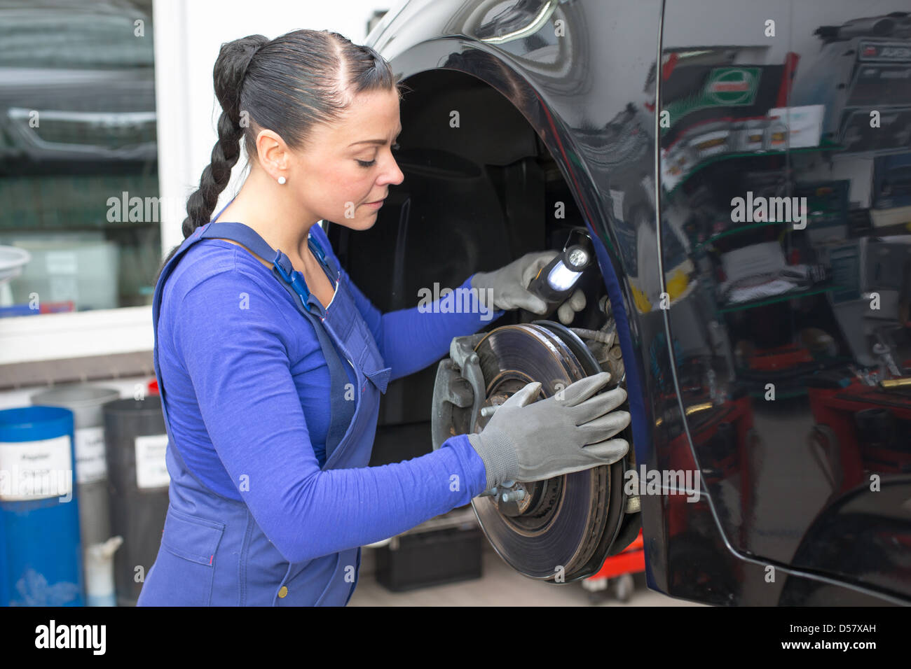 Car mechanic repairs the brakes of an automobile on a hydraulic lift - Stock Image