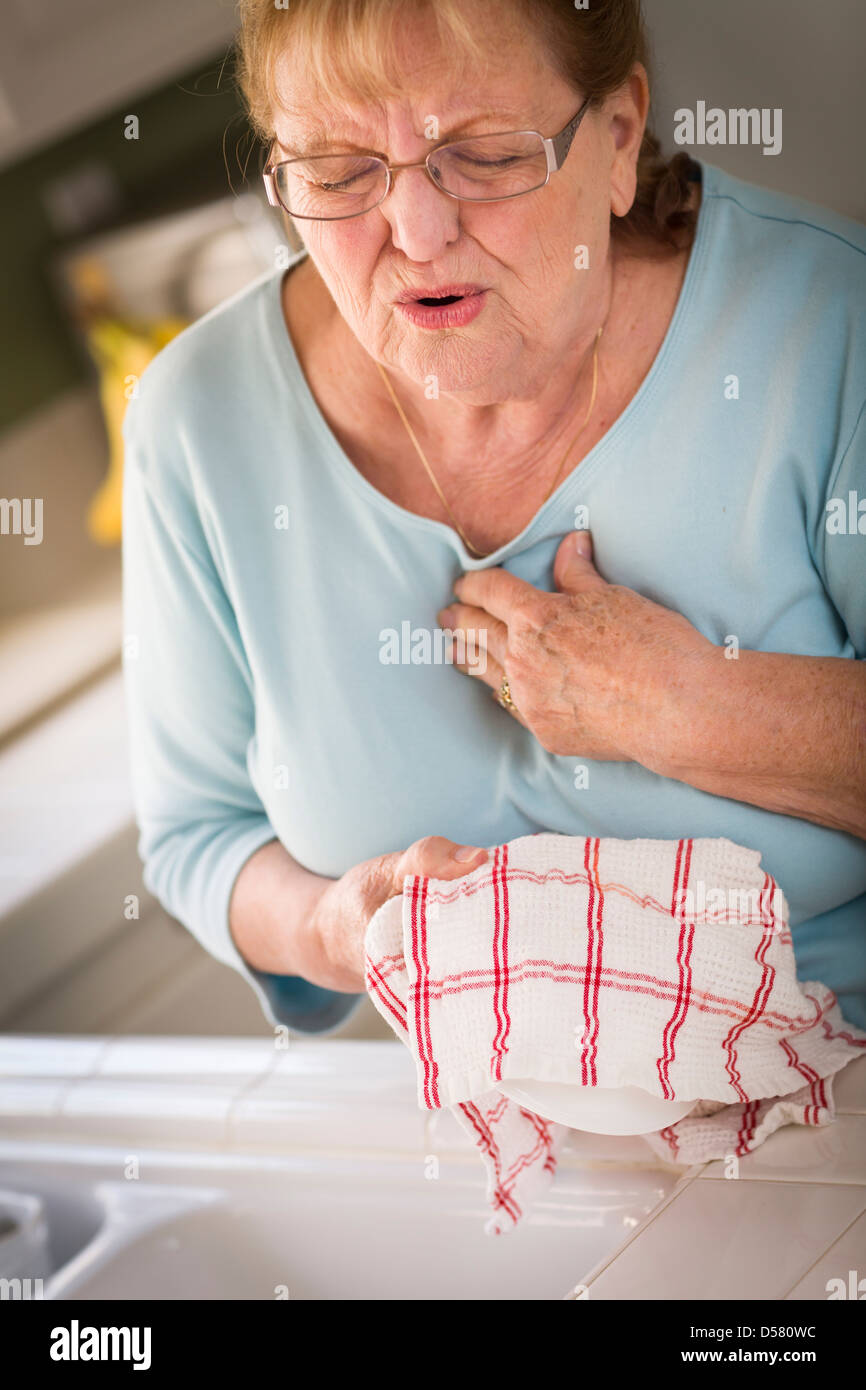 Grimacing Senior Adult Woman At Kitchen Sink With Chest Pains. - Stock Image